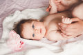 Close-up portrait of cute happy smiling baby girl lying down on bed. Mother is holding her newborn baby. Small daughter Royalty Free Stock Photo