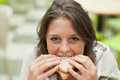 Close up portrait of a female student eating sandwich smiling in the cafeteria Royalty Free Stock Image