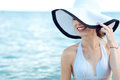 Close up portrait of gorgeous glam smiling lady hiding the half of her face behind the wide brim hat Royalty Free Stock Photo