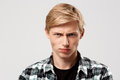 Close up portrait of handsome confident angry blond young man wearing casual plaid shirt looking in camera isolated on Royalty Free Stock Photo