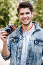 Close-up portrait of a handsome guy holding camera outdoors Royalty Free Stock Photo
