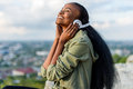 Close-up portrait of happy smiling young black african american woman listening to music. Blurred cityscape on Royalty Free Stock Photo