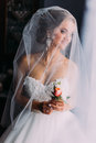 Close up portrait of happy stylish blonde bride in luxury white dress with bouquet under the veil Royalty Free Stock Photo