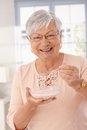 Close up portrait of happy woman eating cereals closeup old lady breakfast cereal smiling looking at camera Stock Images