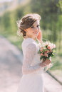 Close up portrait of magical beautiful young bride wearing elegant white dress with bouquet in the park. Royalty Free Stock Photo