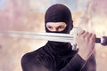 Close up portrait of male ninja with sword outdoor in smoke Royalty Free Stock Photo