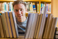 Close up portrait of a male student in the library young amid bookshelves college Royalty Free Stock Photos