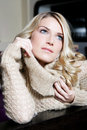 Close up portrait of pensive young blond woman playing with the neck her cardigan pullover Stock Photos