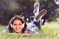 Close up portrait of Pretty young girl listening music lying at the grass Royalty Free Stock Photo