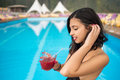 Close-up of portrait profile young brunette woman holding a cocktail on a blurred background of resort swimming pool Royalty Free Stock Photo