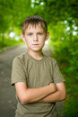 Close up portrait of serious little boy with folded hands outdoo looking at the camera outdoors Stock Image