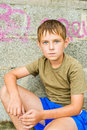 Close up portrait of serious little boy sitting outdoors lokking at the camera Royalty Free Stock Image
