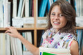 Close up portrait of a smiling female student against bookshelf in the library standing Royalty Free Stock Photography