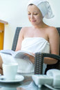 Close up portrait smiling young pretty woman with towel hat se setting of the chair and reading the book against cup coffee and Stock Photo
