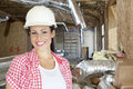 Close-up portrait of smiling young woman contractor at construction site Royalty Free Stock Photo