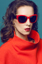 Close up portrait of a stunning female model in red dress and elegant spectacles posing over background beauty fashion optics Stock Photo