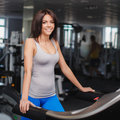 Close up portrait of young attractive woman training on simulator in gym female looking at camera while Stock Photography
