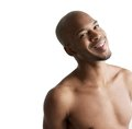 Close up portrait of a young black man smiling shirtless Stock Photos