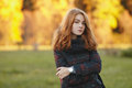 Close up portrait young romantic redhead woman in scarf and plaid jacket against autumn foliage background cold season outdoors Royalty Free Stock Photo