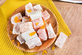 Close-up of a powdered turkish delight. Plate of fruit rahat lokum on a wooden background. Exotic confectionery sweets. Royalty Free Stock Photo