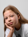Close up of the pre teen girl a is photographed on gray background serene child is looking at camera her fair long hair are Stock Photo