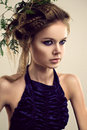 Close up of pretty woman with beauty make up portrait young fashionable hairstyle and dry twig fern in her hair dressed in blue Stock Photo