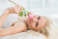 Close up of a pretty woman in bed with a rose young at home Stock Photos
