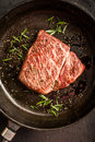 Close up raw wagyu beef striploin steak with pepper on dark pan. Restaurant Royalty Free Stock Photo