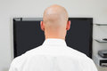 Close up rear view of a bald man using computer at office Stock Photo