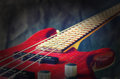 Close-up red bass guitar on dark background. Vintage toning with vignette Royalty Free Stock Photo