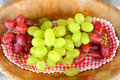 Close up of red and gree grapes on a wooden plate green wood doily Stock Images