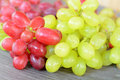 Close up of red and gree grapes on a wooden plate green wood doily Royalty Free Stock Photos