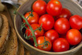 Close up of red tomatoes in a green bowl and slices of bread Royalty Free Stock Photos