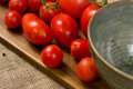 Close up of red tomatoes and a green bowl on wood and canvas Royalty Free Stock Photo