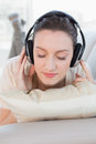 Close up of a relaxed casual woman enjoying music on sofa young in bright house Stock Photo