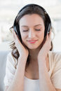 Close up of relaxed casual woman enjoying music a young in a bright house Stock Images