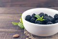 Close up of ripe blackberries in a white ceramic bowl over rusti Royalty Free Stock Photo