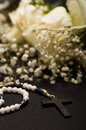 Close up of a rosary beads with blurred white small flowers with a withe rose behind, black background Royalty Free Stock Photo