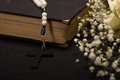 Close up of a rosary beads over a holy bible with blurred white small flowers, black background Royalty Free Stock Photo
