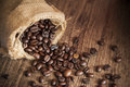 Close-up rost coffee seed and sack on wood table Royalty Free Stock Photo
