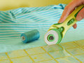 Close up of rotary cutter cutting fabric with Stock Photos