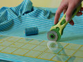Close up of rotary cutter cutting fabric with Royalty Free Stock Photo