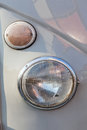 Close-up round headlight of shiny grey vintage retro car. Royalty Free Stock Photo