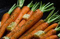Close up of rustic carrotts in a pan with butter on wood image carrots and herbs Stock Images