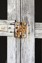 Close up rusty hinge on white gate faded Stock Photo