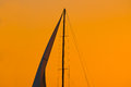 Close up of a sail silhouette under an orange sky at sunset Royalty Free Stock Photo