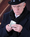 Close up scrooge image of the miserly mr looking suspiciously while holding a fistful of dollar bills Stock Photos