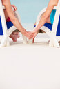 Close up of senior couple holding hands beach in chairs holding hands Stock Images