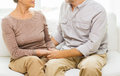 Close up of senior couple holding hands at home family relations age and people concept happy on sofa Stock Photography