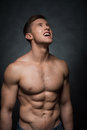 Close up of sexy fit man looking up standing topless isolated over dark background Royalty Free Stock Image